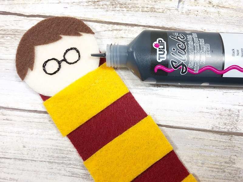 Draw Harry's glasses onto his face with black dimensional fabric paint Creatively Beth #creativelybeth #harrypottercrafts #harrypotter #feltcrafts #kidscrafts