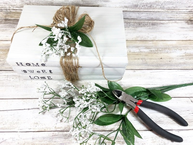 Clip a section of flowers from a dollar tree branch and tuck into twine How to DIY Book Stack Creatively Beth #creativelybeth #dollartreecraft #homedecor #bookstack #diy