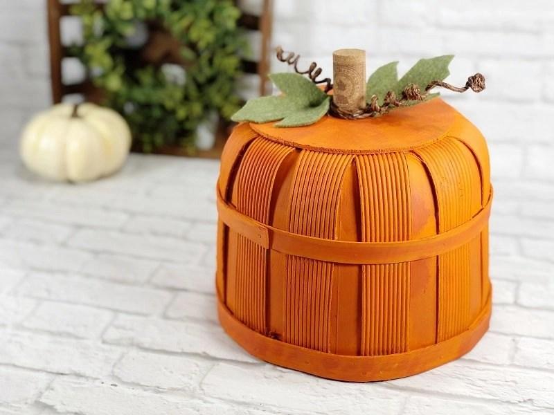 How to make a DIY Pumpkin Bushel Basket Fall Decor with orange paint, a wine cork ste, wite vines and felt leaves on a white background Creatively Beth #creativelybeth #dollartree #craft #falldecor #bushelbasket #pumpkin #craft