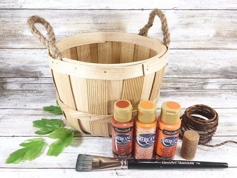 Materials needed for How to make a DIY Pumpkin Bushel Basket Fall Decor with orange paint, a wine cork ste, wite vines and felt leaves on a white background Creatively Beth #creativelybeth #dollartree #craft #falldecor #bushelbasket #pumpkin #craft