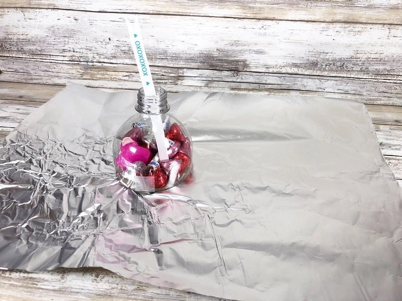 Roll out and cut a piece of aluminum foil that is square Creatively Beth #creativelybeth #valentinesday #hersheykiss #recycledcrafts