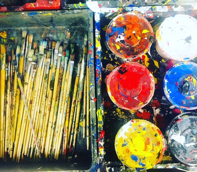 Paint pots and a pile of brushes