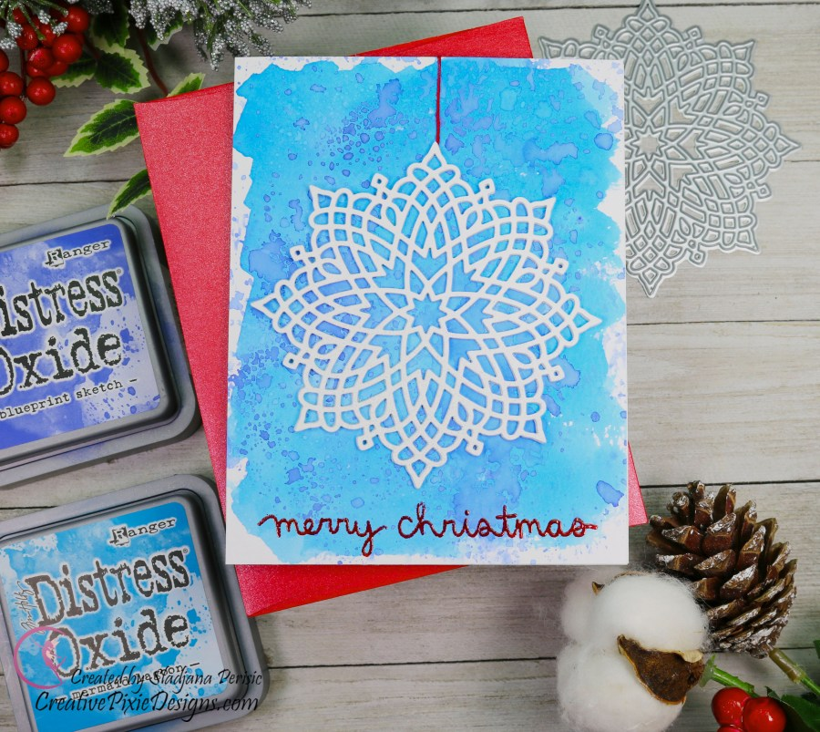 A clean and simple Merry Christmas handmade card featuring MFT Captivating Mandala die set against an ink water colored background.