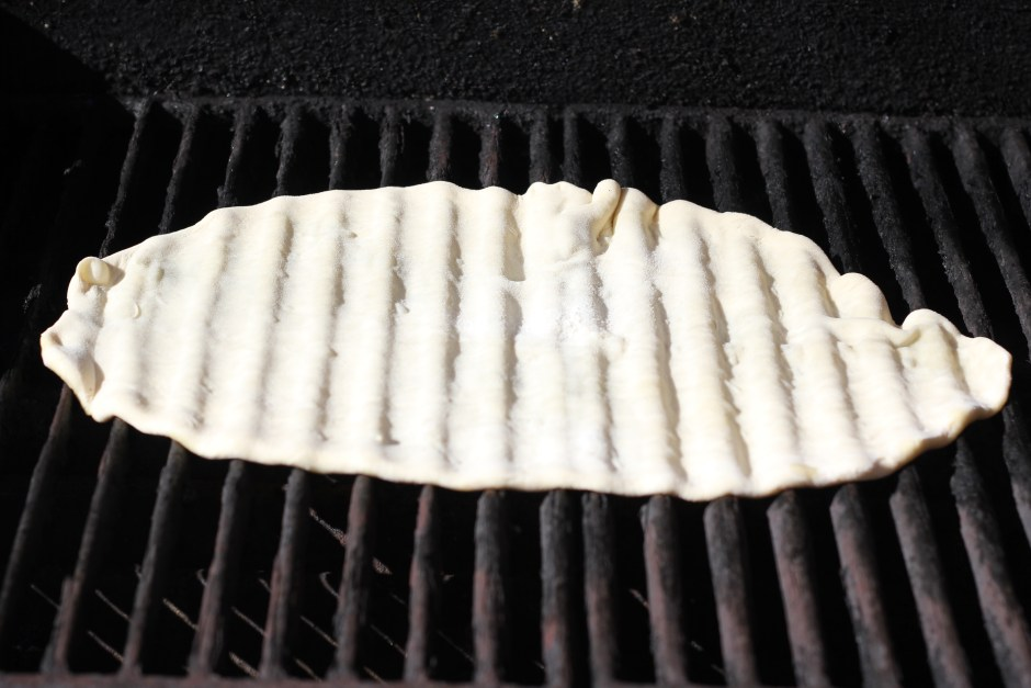 Rolled out pizza dough on the grill.