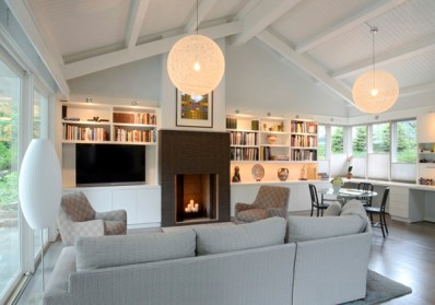 The fireplace surrounded by the TV and bookcase create a focal point. The tall fireplace draws your eye up to the ceiling details.