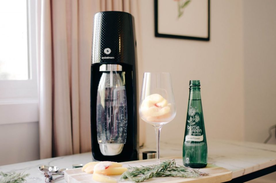 Showing how to make an edlerflower, peach and rosemary sparkling water drink recipe using a SodaStream