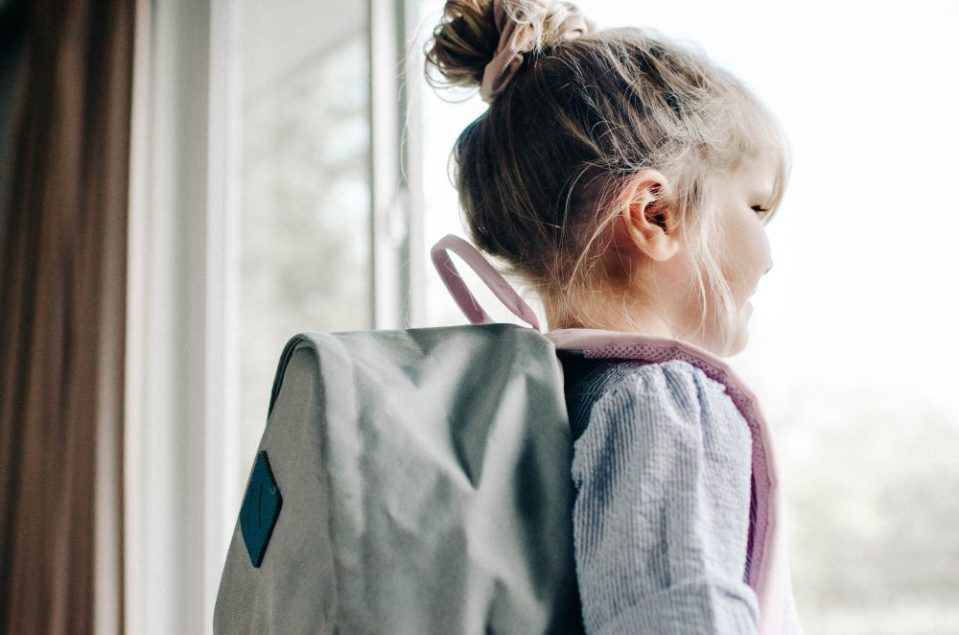 Girl with her back pack on looking outside for back-to-school