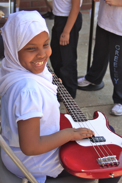 Young woman smiles with an electric guitar resting on her lap, her right hand lightly laying on the strings. Photo courtesy: Urban Gateways, Chicago, IL. Image by: Carrie Rosales.