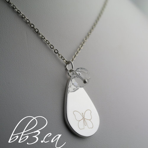 silver teardrop necklace with manually engraved butterfly and clear glass bead