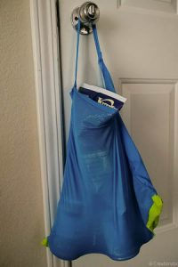 upcycled shopping bag filled with groceries and hanging on a doorknob