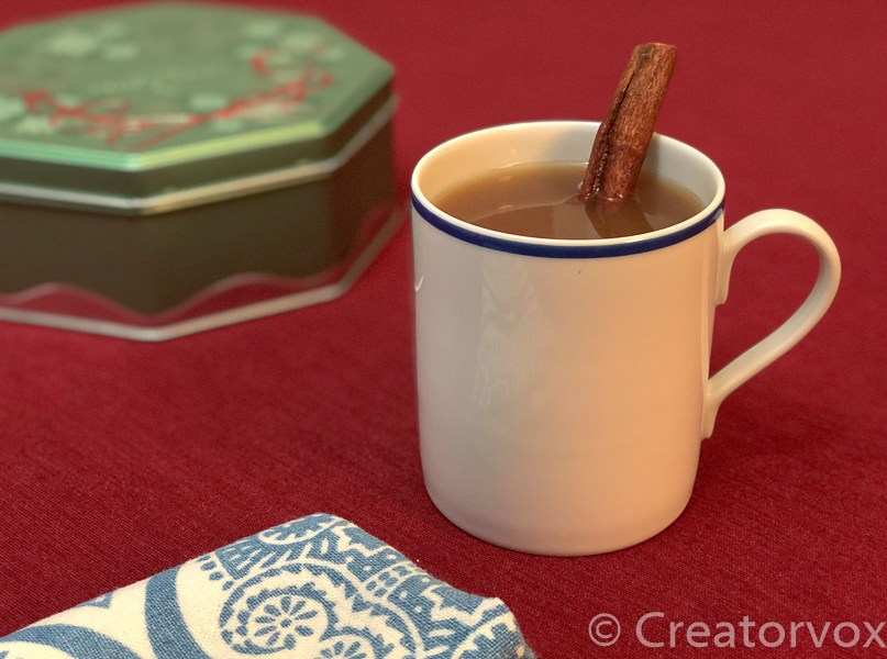 cup of hot apple cider and a cookie tin