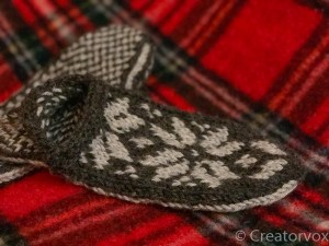 knitted slippers with snowflake pattern on a tartan blanket