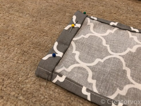 pinning the tube for the drawstring at the top of a bag