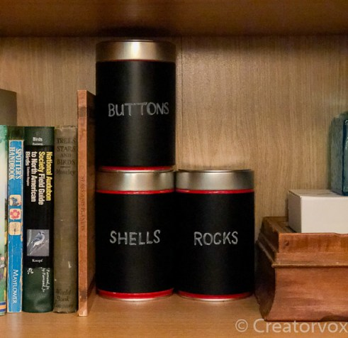 three coffee cans covered in black contact paper, labeled with chalk, on a bookshelf
