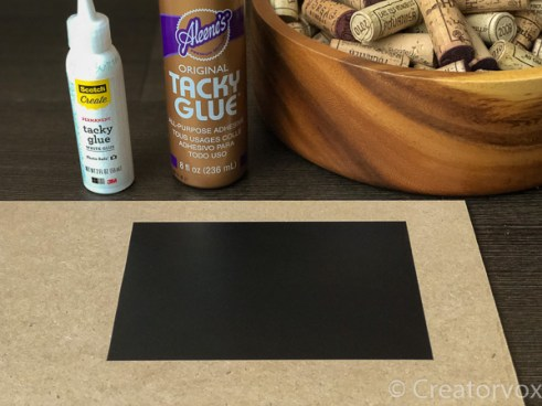 small sheet of contact paper stuck to MDF with corks and glue bottles in the background