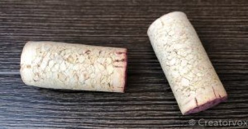 two very light-colored corks without any printing or marks on them