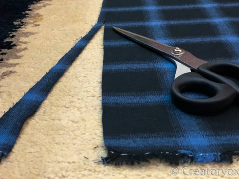 fabric scarf being cut to size