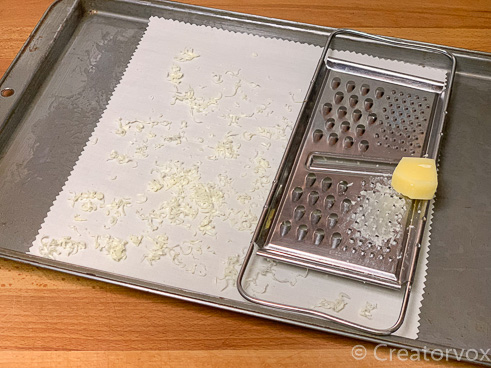 grate beeswax over fabric on baking tray