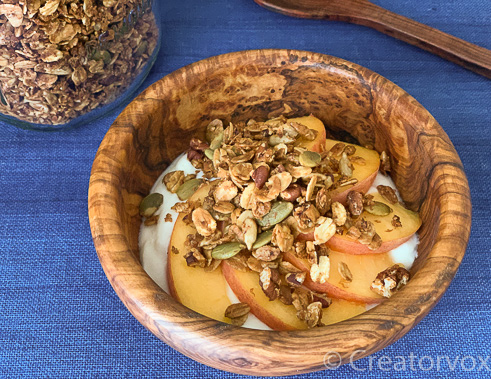 bowl of homemade breakfast granola with yogurt and fruit