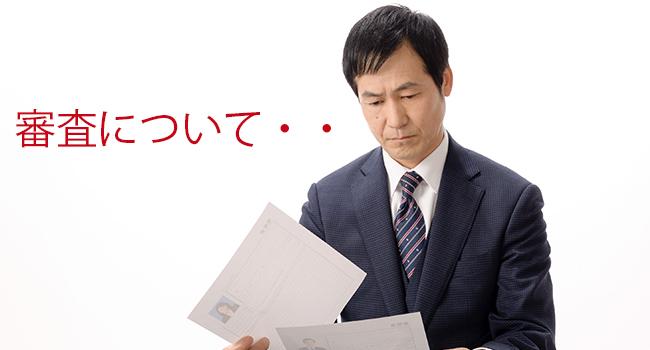 スーツの中年男性が厳しい目で書類を見ている