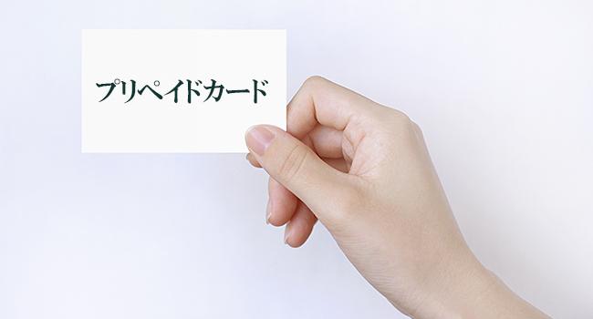 プリペイドカードと書かれた紙を持つ手