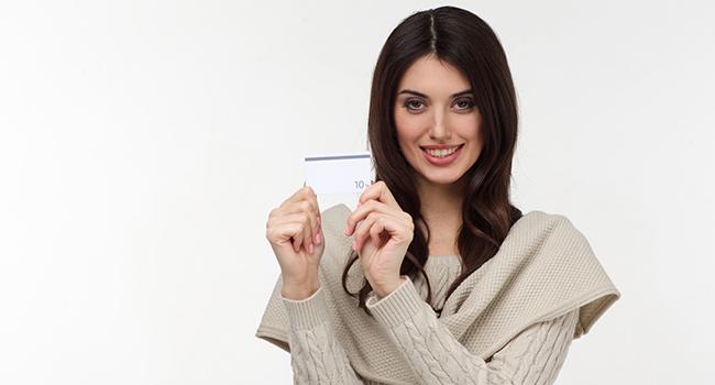 クレジットカードを見せている笑顔の女性