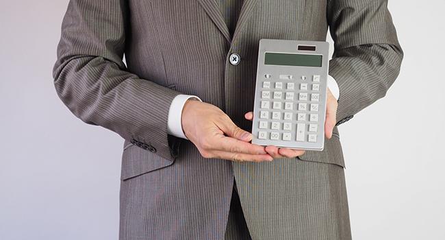 計算機を見せているスーツの男性