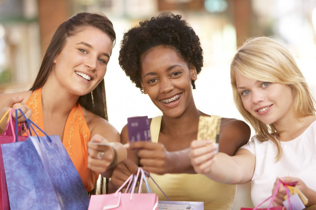 Teens shopping with credit cards; a parent can sign up their teen as an authorized credit card user.