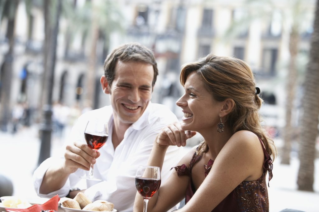 Couple drinking wine at outdoor cafe purchased with their Chase Sapphire Preferred card.