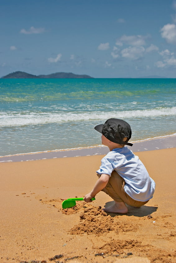 Young boy playing in beach sand