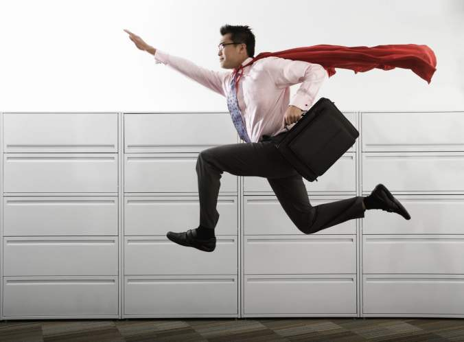 Businessman Leaping and Wearing Red Cape