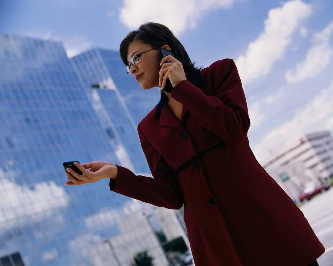 Businesswoman on Cell phone and Holding Pager