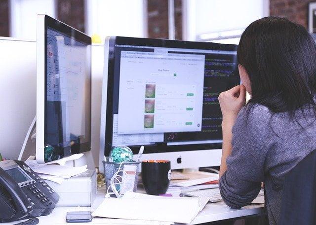 Woman at Dual-Screen Computer