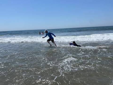 Joe Winn Pulling Child on Board Through Surf