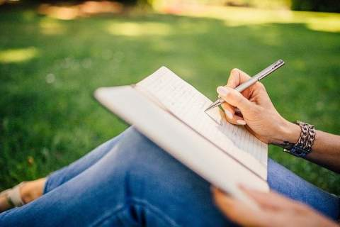 Person Writing in Notebook in Park