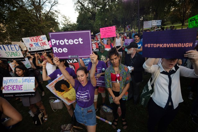 """Group of protesters with signs that say """"Protect Roe"""" and """"Stop Kavanaugh"""""""