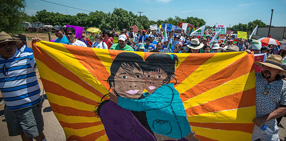 Detention Watch Network protest with members holding a brightly painted banner of a mother and child of color hugging