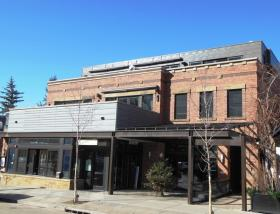 Image:  the front of a brick building with a restaurant patio and covered entryway.