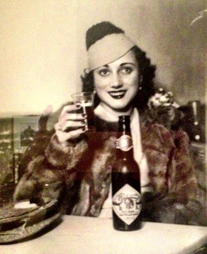 Photo: brown & white photo of well-dressed woman in make-up and a fashionable hat with a bottle in front of her holding up a shot glass.