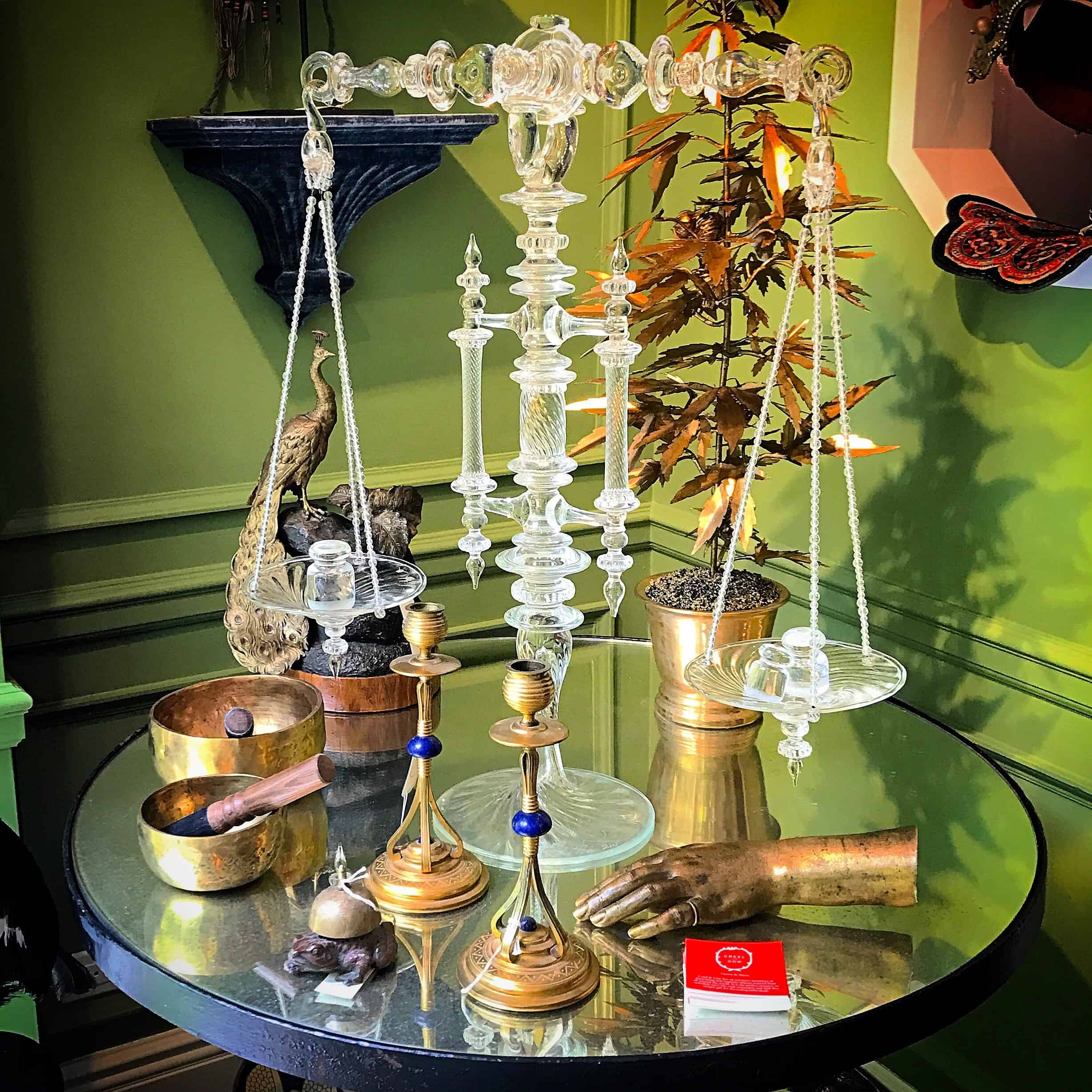 Interior with Table in front of green wall with glass scale, candlesticks, bronze hand