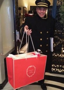 Doorman in cap holding Creel and Gow Red Bag