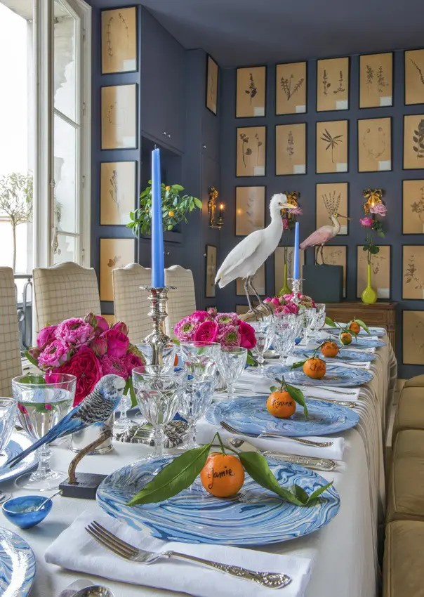 Set table with white table cloth, place settings with blue plates and orange fruit on top.  Table shows taxidermy birds and pink floral arrangements.