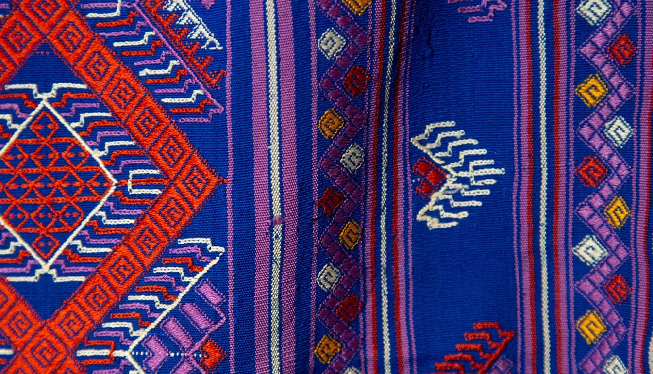 closeup of Large Blue Textile with red and white diamond zig-zag pattern with multicolor geometric designs