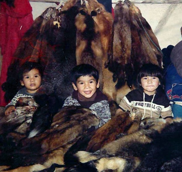Three little sons of Billy Isaacs, Jr. of Moose Factory, sitting in front of a good season's worth of pelts around 1983.