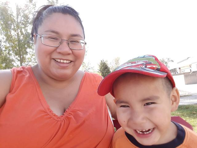 Crystal Anderson - from Fox Lake, Manitoba, and her baby boy Trenton, looking great in orange.