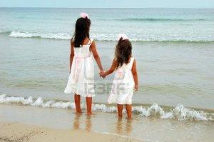 1525376-las-ninas-vestidos-de-blanco-en-la-mano-por-la-playa