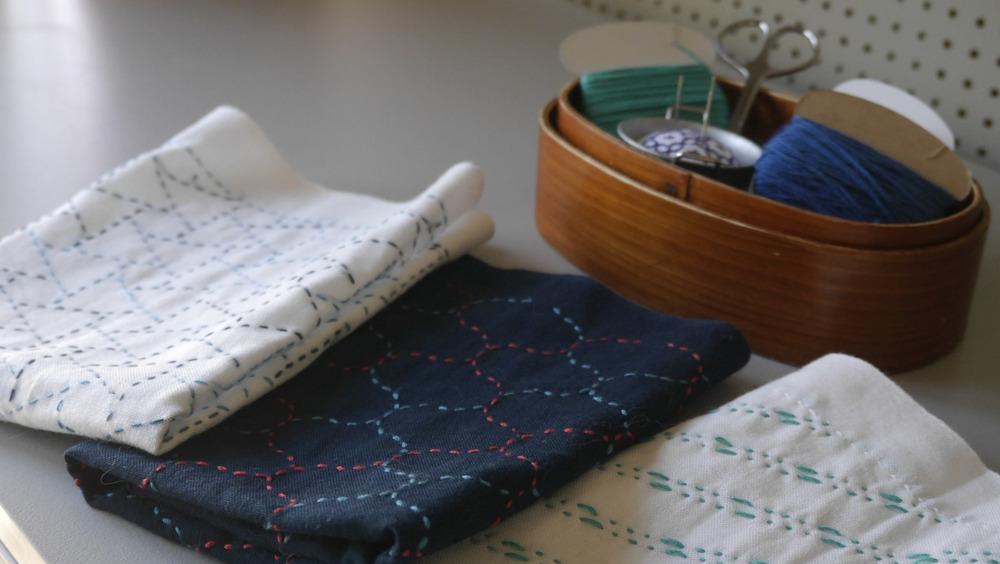 broderie sashiko fait main sur tissu blanc, indigo et crème
