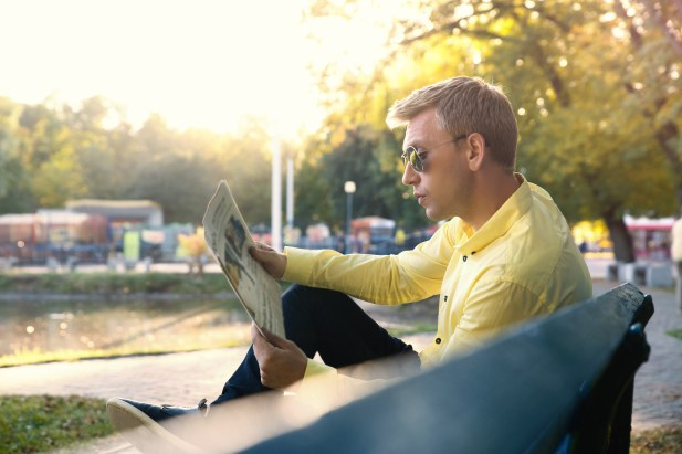 Young man reading a newspaper on a bench. Warm autumn day.