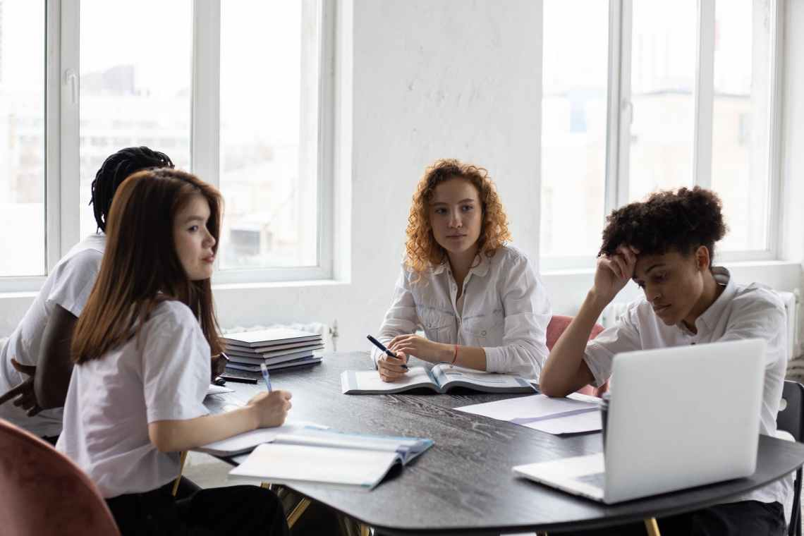 concentrated diverse colleagues brainstorming together in office