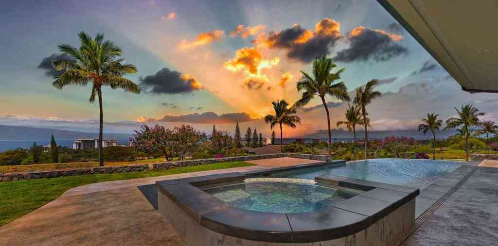 Sunset view from jacuzzi and pool of luxury Maui home by Crescent Homes Maui.